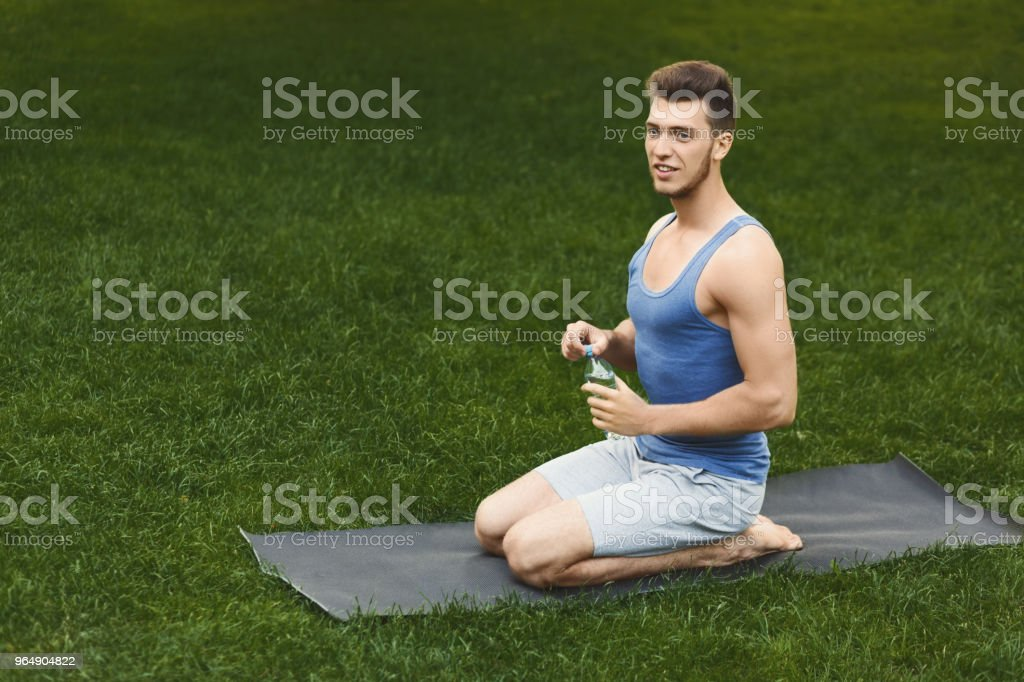 Young man drinking water during training outdoors royalty-free stock photo