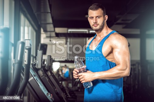 istock Young man drinking water in gym 480281096