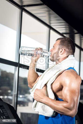 istock Young man drinking water in gym 480281100