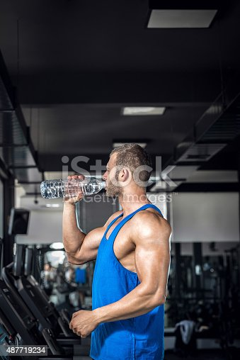istock Young man drinking water in gym 487719234