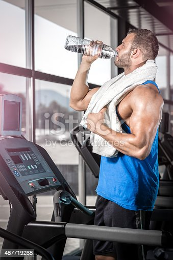 istock Young man drinking water in gym 487719268