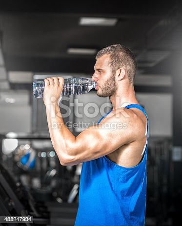 istock Young man drinking water in gym 488247934