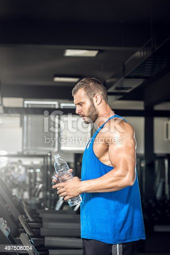 istock Young man drinking water in gym 497508024