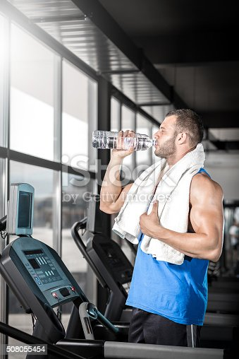 istock Young man drinking water in gym 508055454