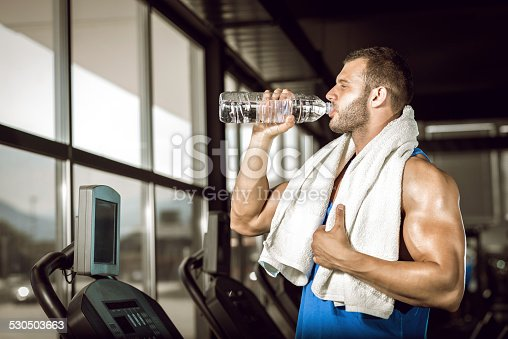 istock Young man drinking water in gym 530503663