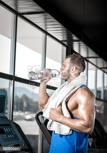 istock Young man drinking water in gym 530504441