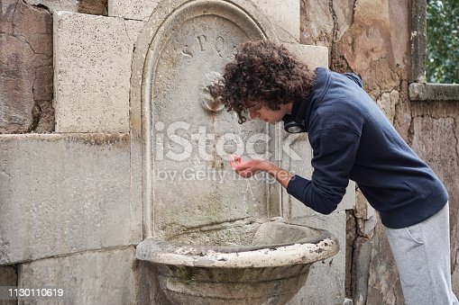 Young man drinking water in Rome. About 25 years old, Caucasian male with curly hair.