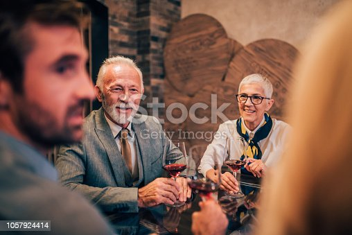 istock Young man drinking wine with family 1057924414