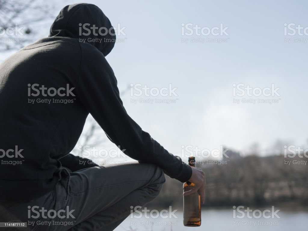 A young man drinks alcohol outdoors. Loneliness, problems in life.