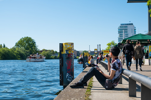 Young man drinks beer at riverside at river Spree, Berlin Wall (East side Gallery ) on a sunny day