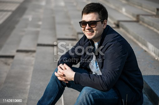 665586146 istock photo A young man drinks coffee in the city and walks outside. 1142610660