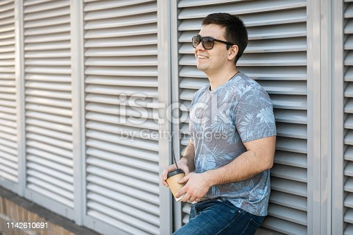 665586146 istock photo A young man drinks coffee in the city and walks outside. 1142610691