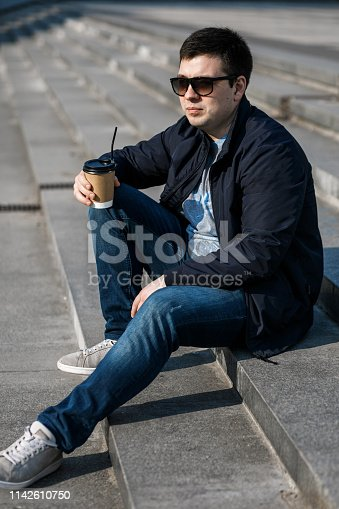 665586146 istock photo A young man drinks coffee in the city and walks outside. 1142610750