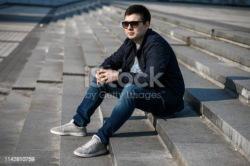 665586146istockphoto A young man drinks coffee in the city and walks outside. 1142610759