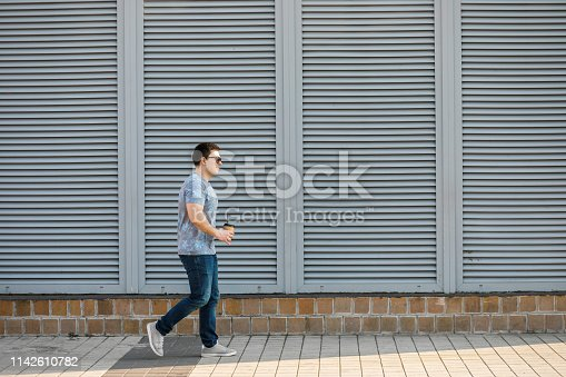 665586146 istock photo A young man drinks coffee in the city and walks outside. 1142610782