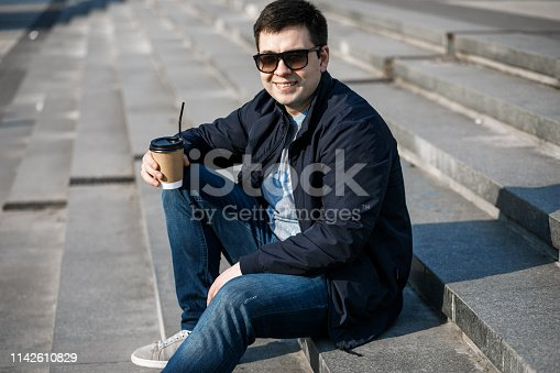 665586146 istock photo A young man drinks coffee in the city and walks outside. 1142610829
