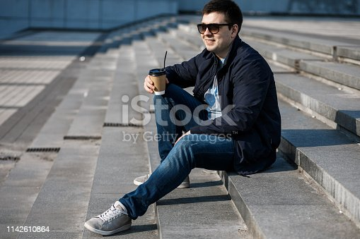 665586146 istock photo A young man drinks coffee in the city and walks outside. 1142610864