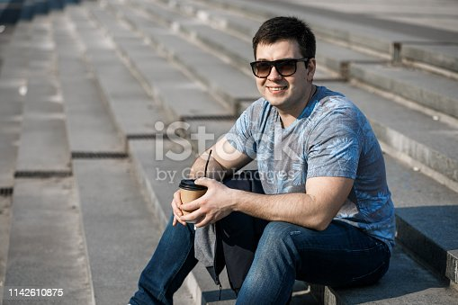 665586146 istock photo A young man drinks coffee in the city and walks outside. 1142610875