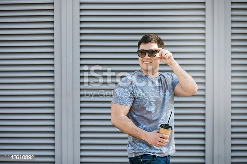 665586146 istock photo A young man drinks coffee in the city and walks outside. 1142610892