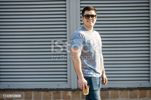 665586146 istock photo A young man drinks coffee in the city and walks outside. 1142610909