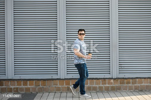 665586146 istock photo A young man drinks coffee in the city and walks outside. 1142610931