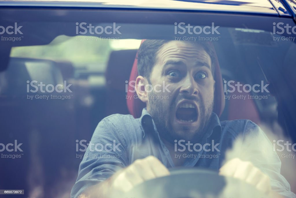 Young man driving a car shocked about to have traffic accident, windshield view stock photo