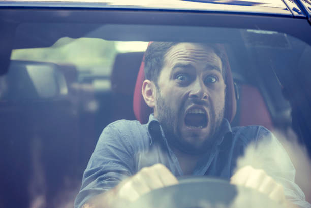 young man driving a car shocked about to have traffic accident, windshield view - impaired driving stock photos and pictures