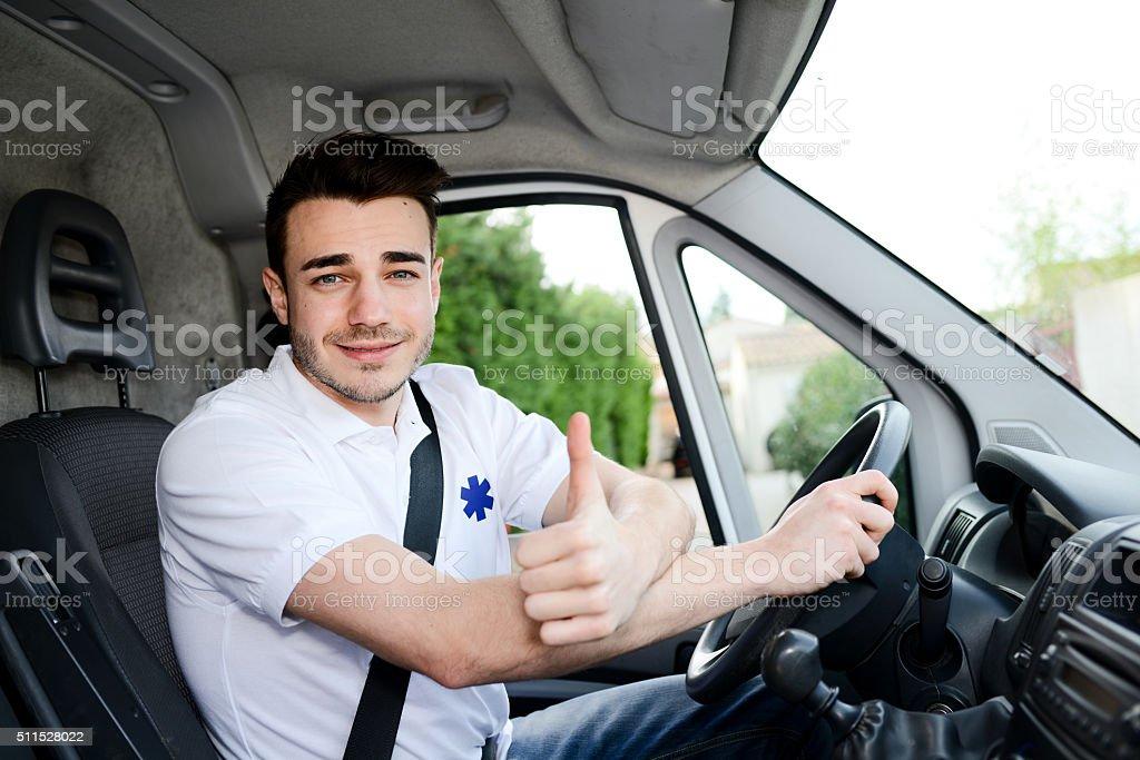 Jeune homme au volant d'ambulance de transport auxiliaire médical - Photo