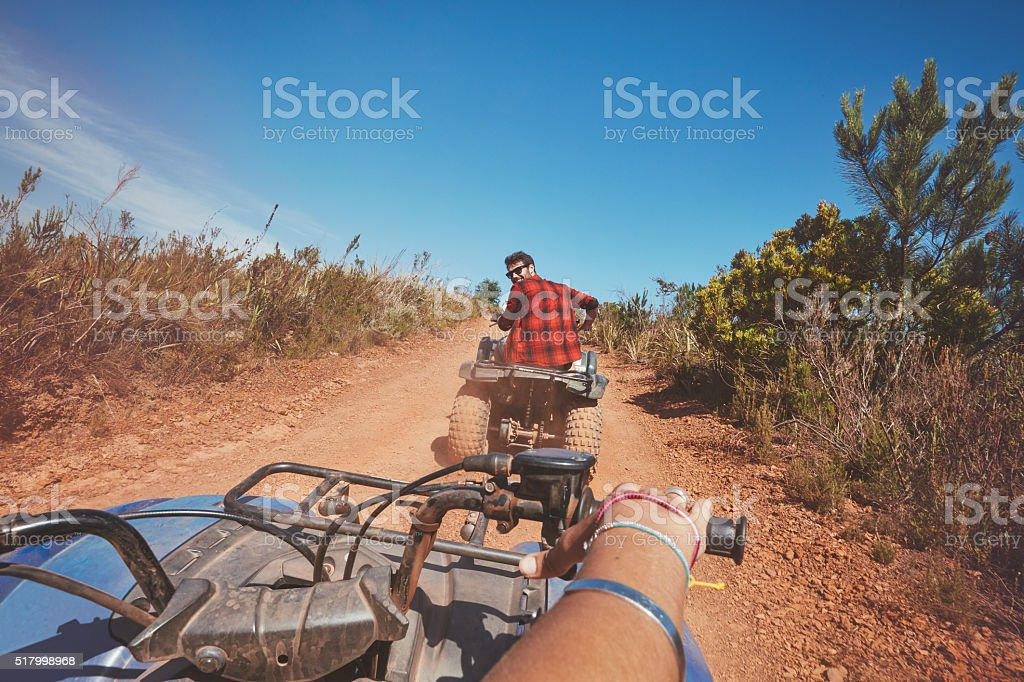 Young man driving ATV in nature stock photo