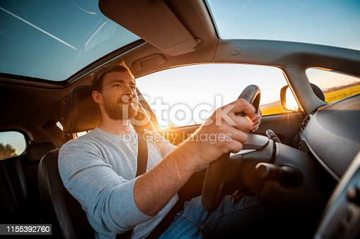 Young man in a car. He is driving, smiling and looking out. Sun is shining from back on  a sunny spring afternoon.