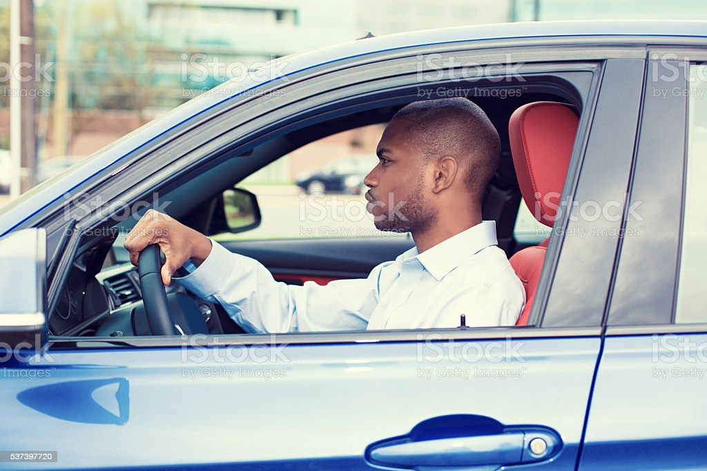 young man driving his new car Closeup portrait young man driving his new car. Personal transportation auto purchase safety concept Adult Stock Photo