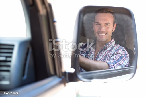1051147634 istock photo Young man driving with his reflection in rear view mirror 664889624