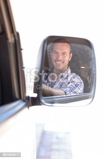 1051147634 istock photo Young man driving with his reflection in rear view mirror 664889672