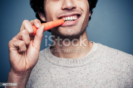 Young multi racial man is eating a carrot