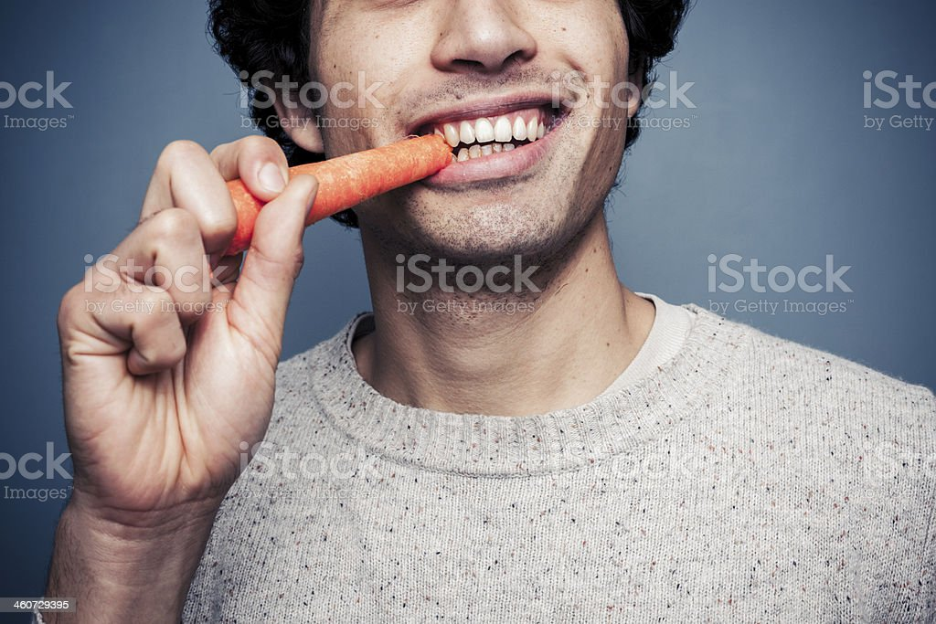 Young man eating a carrot stock photo