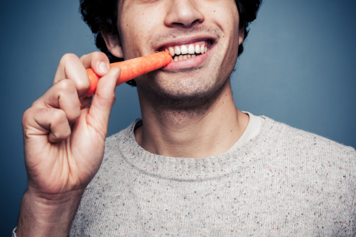 Young Man Eating A Carrot Stock Photo - Download Image Now