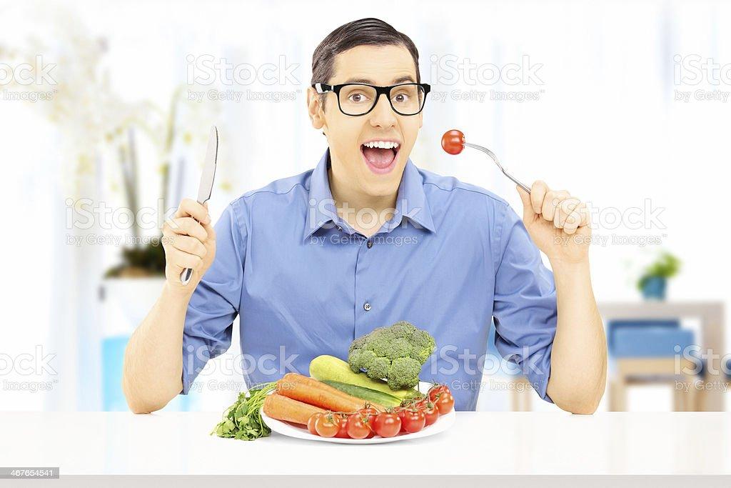 Hombre joven comiendo comida saludable en su hogar - Foto de stock de 20 a 29 años libre de derechos