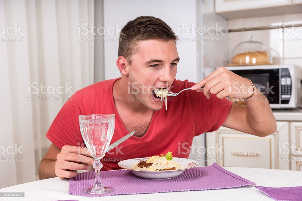 Young man eating a plate of spaghetti stock photo