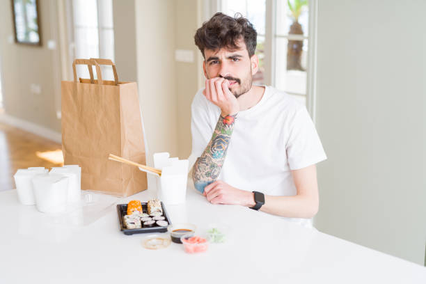 young man eating asian sushi from home delivery looking stressed and nervous with hands on mouth biting nails. anxiety problem. - food delivery стоковые фото и изображения