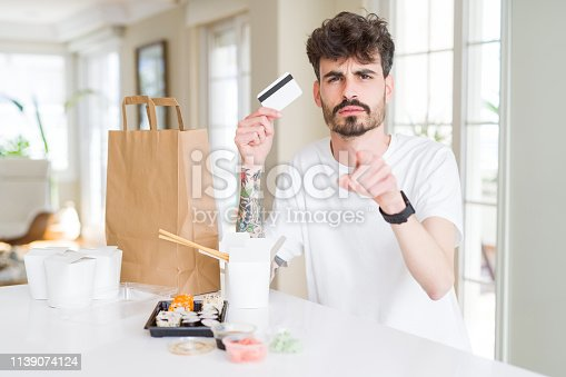 Young man eating asian sushi from home delivery using credit card as payment pointing with finger to the camera and to you, hand sign, positive and confident gesture from the front