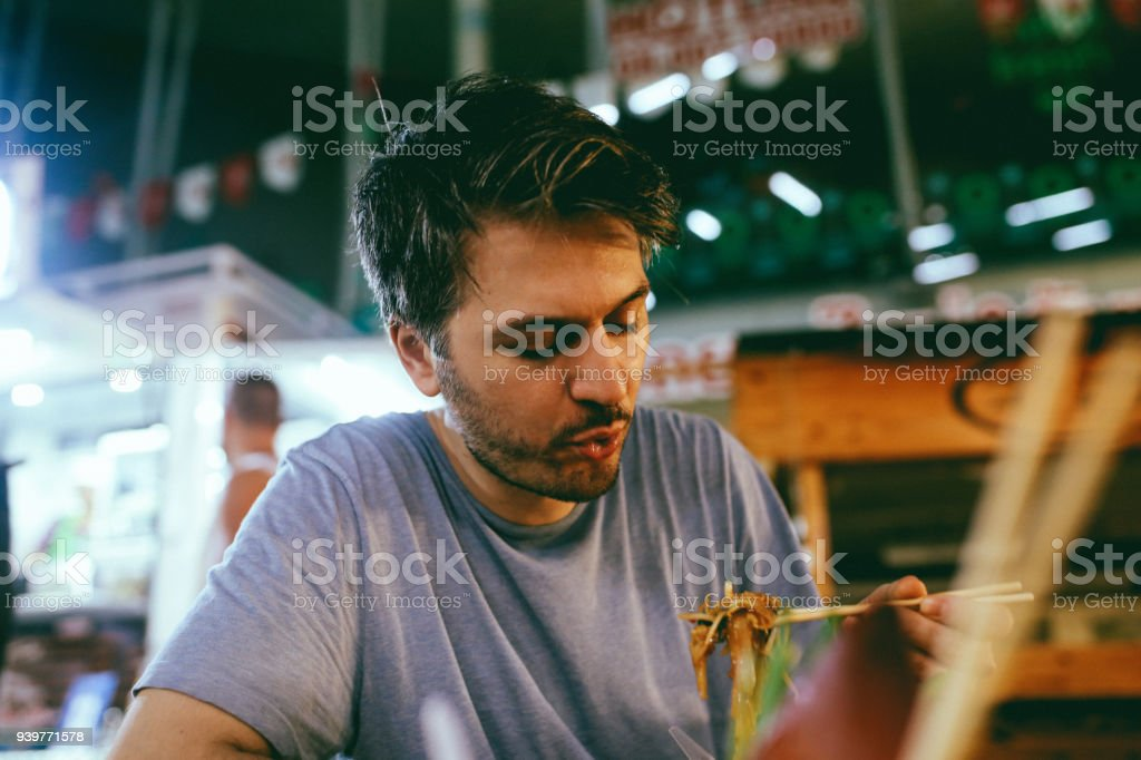 Young man eating authentic Thai food on a street market in Bangkok, Thailand stock photo
