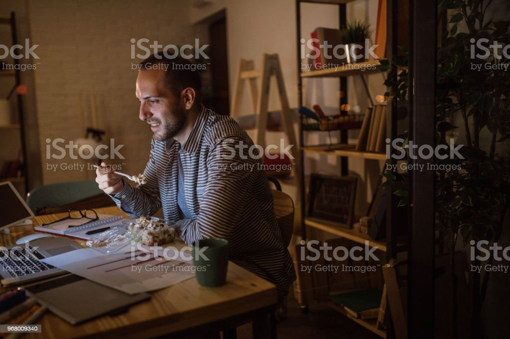 Photo of young man working and eating fast food in the office