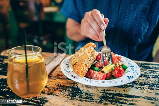 Young man eating healthy fresh salad on a wooden table.