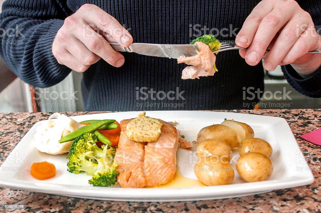 Young man eating salmon steak and vegetables in restaurant - Royaltyfri 20-29 år Bildbanksbilder