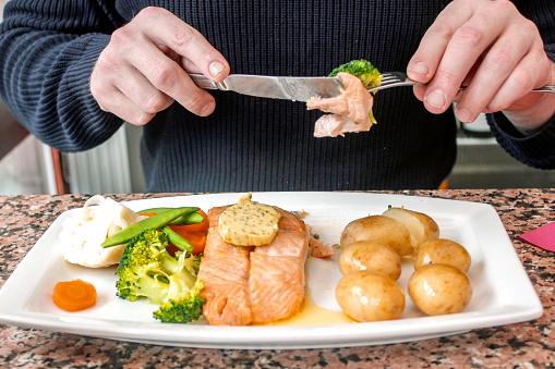 Young Man Eating Salmon Steak And Vegetables In Restaurant-foton och fler bilder på 20-29 år