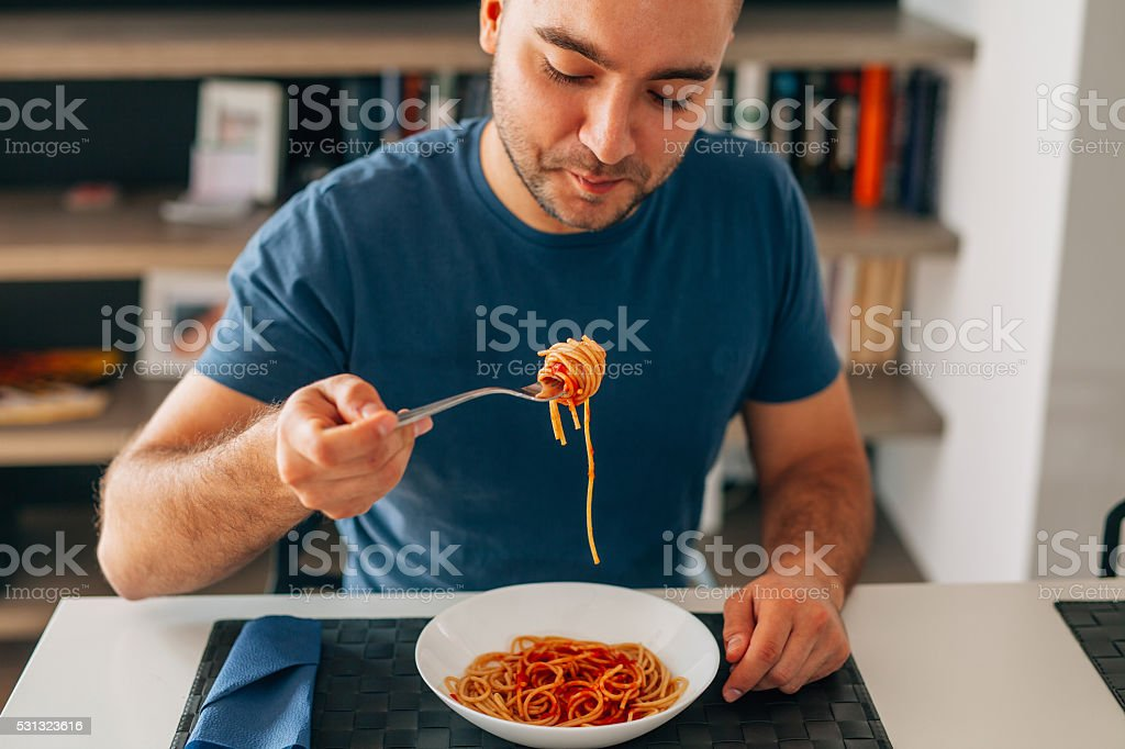 Young man eating spaghetti bolognese. stock photo