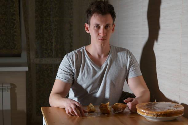 junger mann isst süßigkeiten in der küche in der nacht - mädchen night snacks stock-fotos und bilder