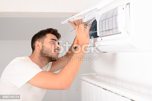 istock young man electrician installer working and cleaning air filter on a indoor unit air conditioner at client's home 836249124