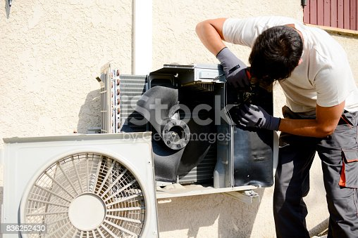895571294 istock photo young man electrician installer working on outdoor compressor unit air conditioner at a client's home 836252430