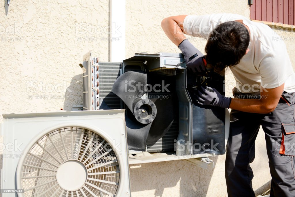 young man electrician installer working on outdoor compressor unit air conditioner at a client's home stock photo